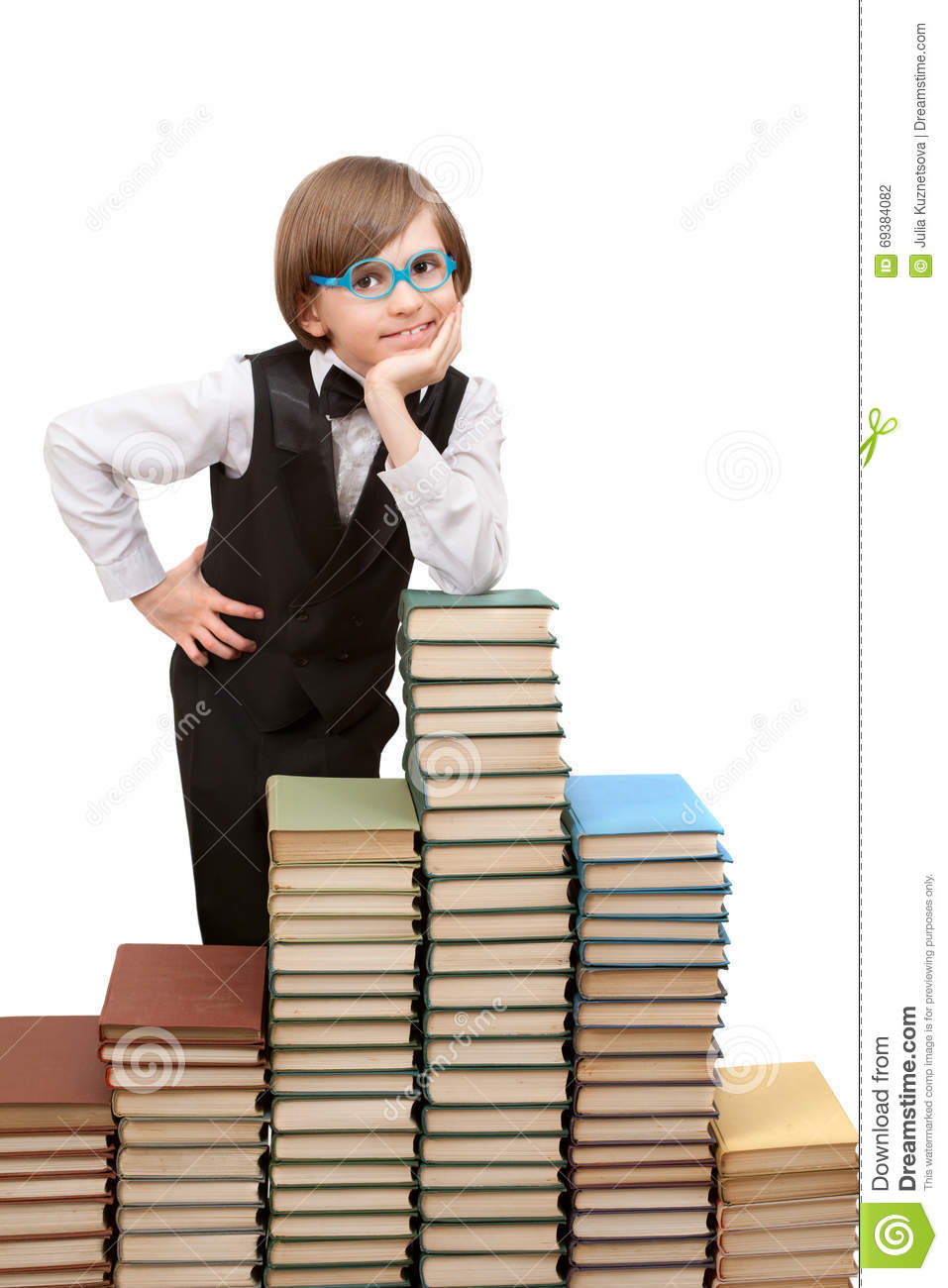 A seven years boy is standing at big stack of books