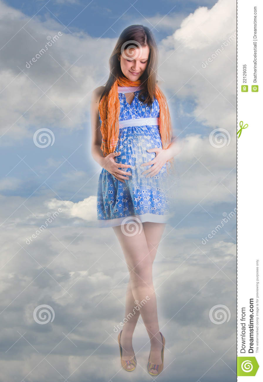 Young beautiful pregnant woman in blue dress is holding her pregnant