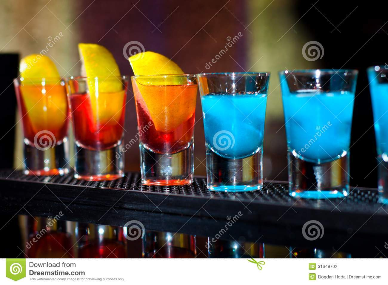several alcoholic shots of diferent drinks at a party