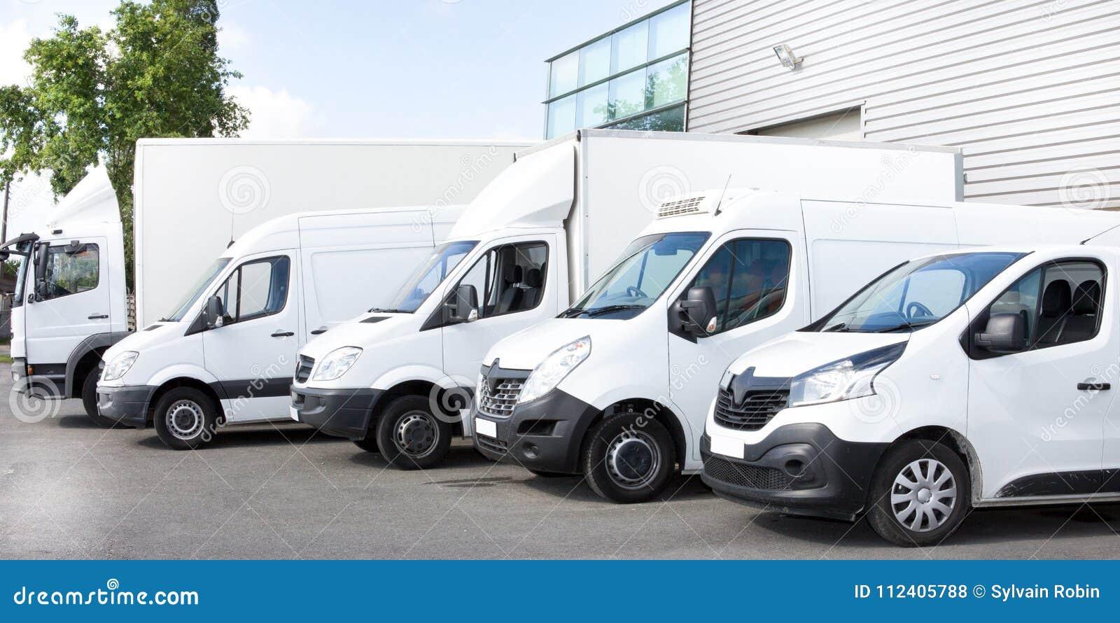 Several cars vans trucks parked in parking lot for rent