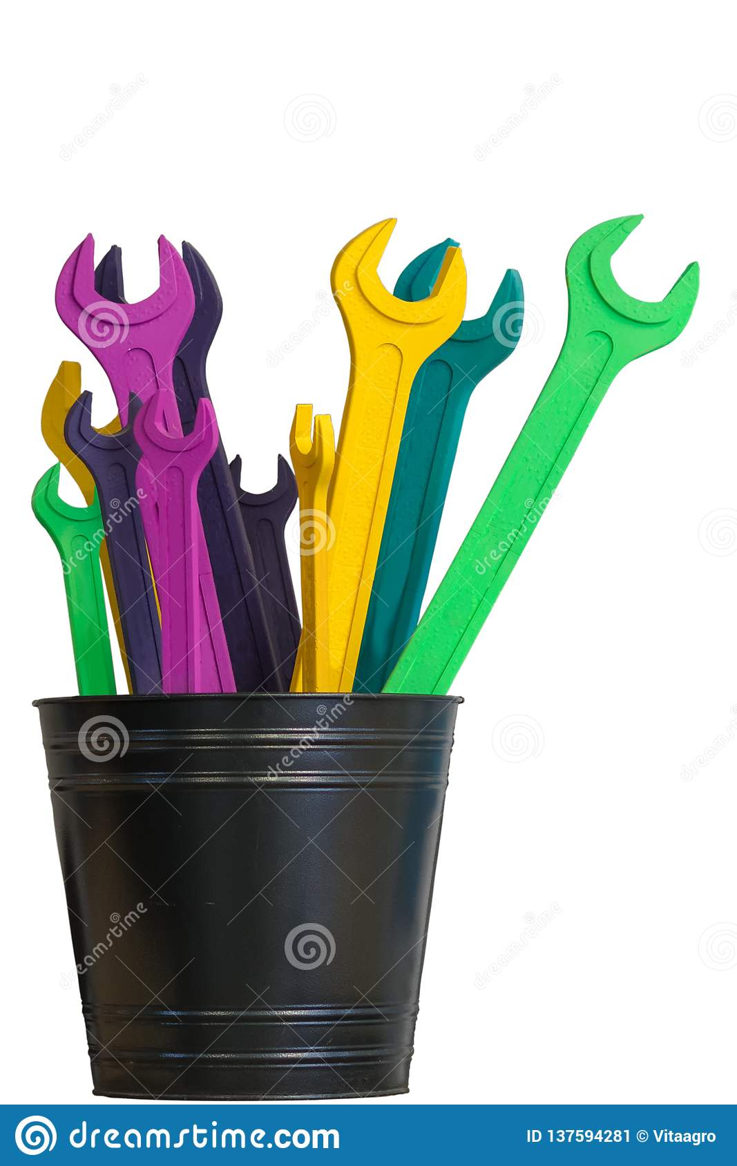 Several colored open end wrenches stand in a black bucket isolated on a white background
