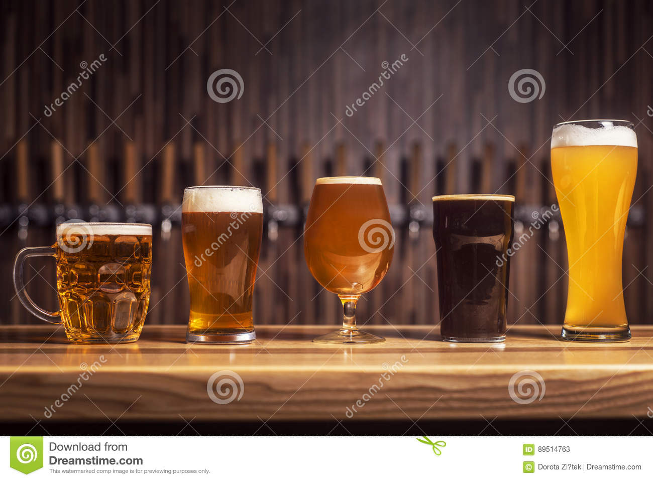 Several different beers are standing in a row at the bar