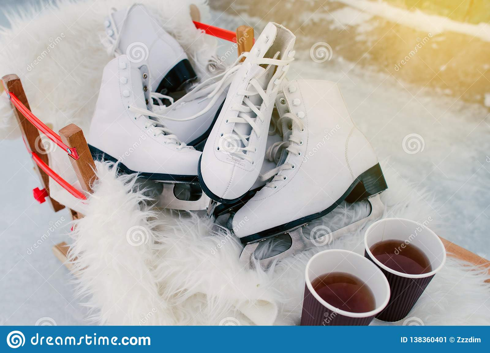 Several Pairs Of Ice Skates With 2 Cups Of Coffie Standing On The