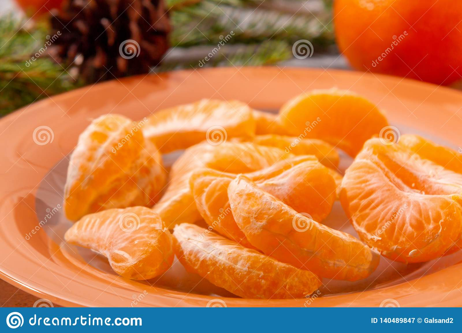 Several peeled tangerine slices on an orange plate with tree branches and a cone-a traditional Christmas and new year`s