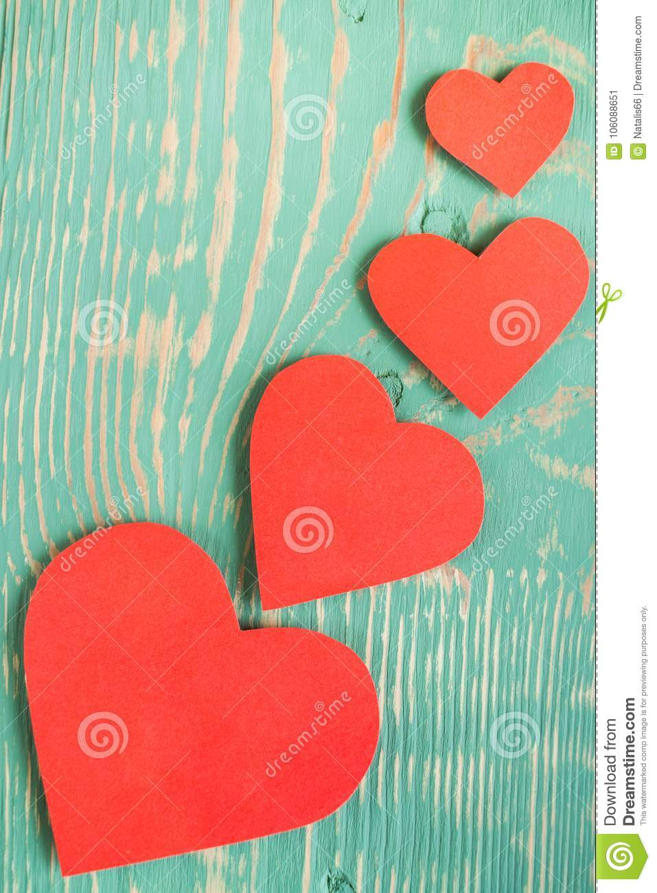 Several red paper hearts on light green painted textured with squiggly stripes wooden table.