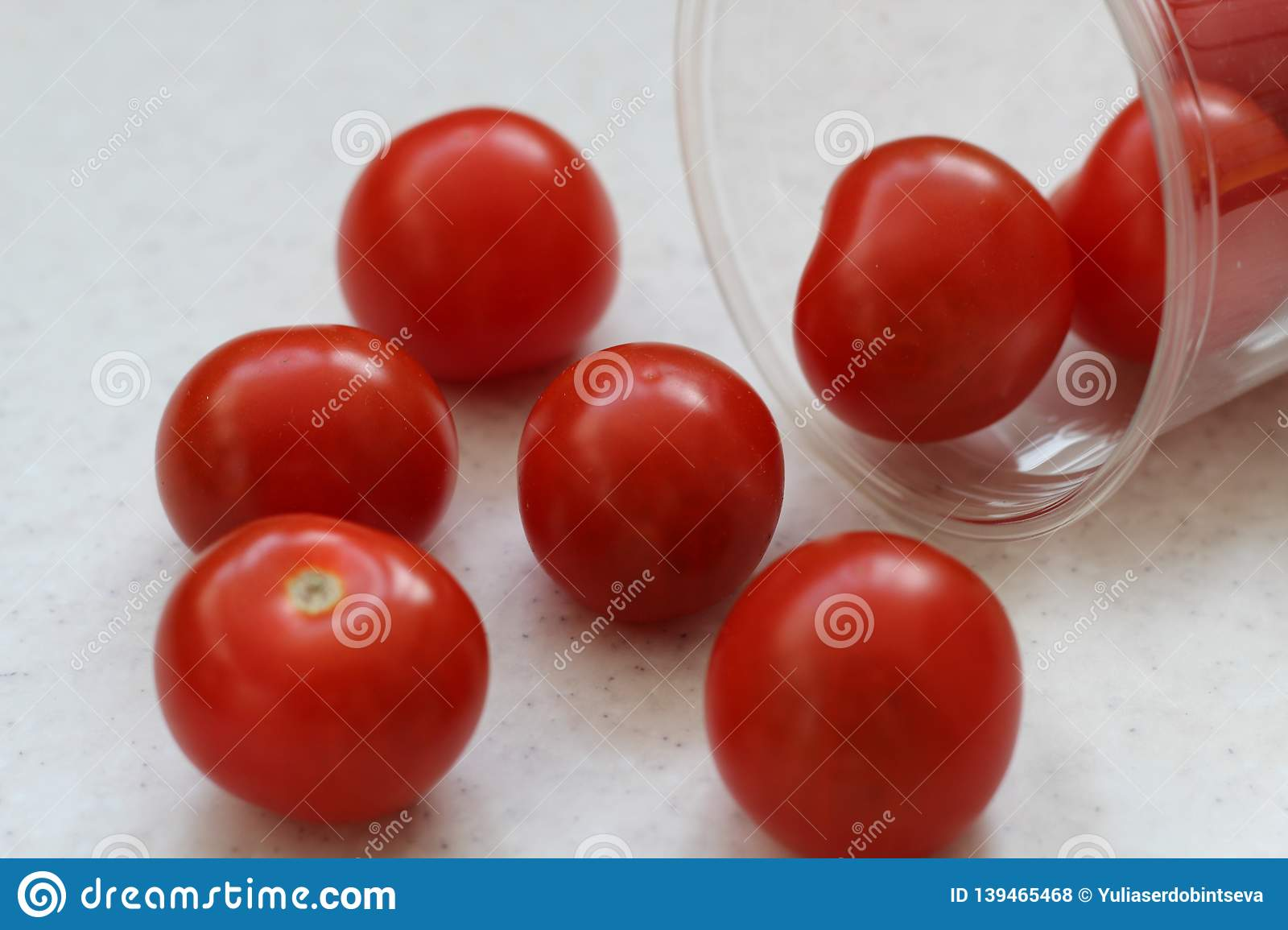 Several red ripe cherry tomatoes rolled out of a plastic transparent glass