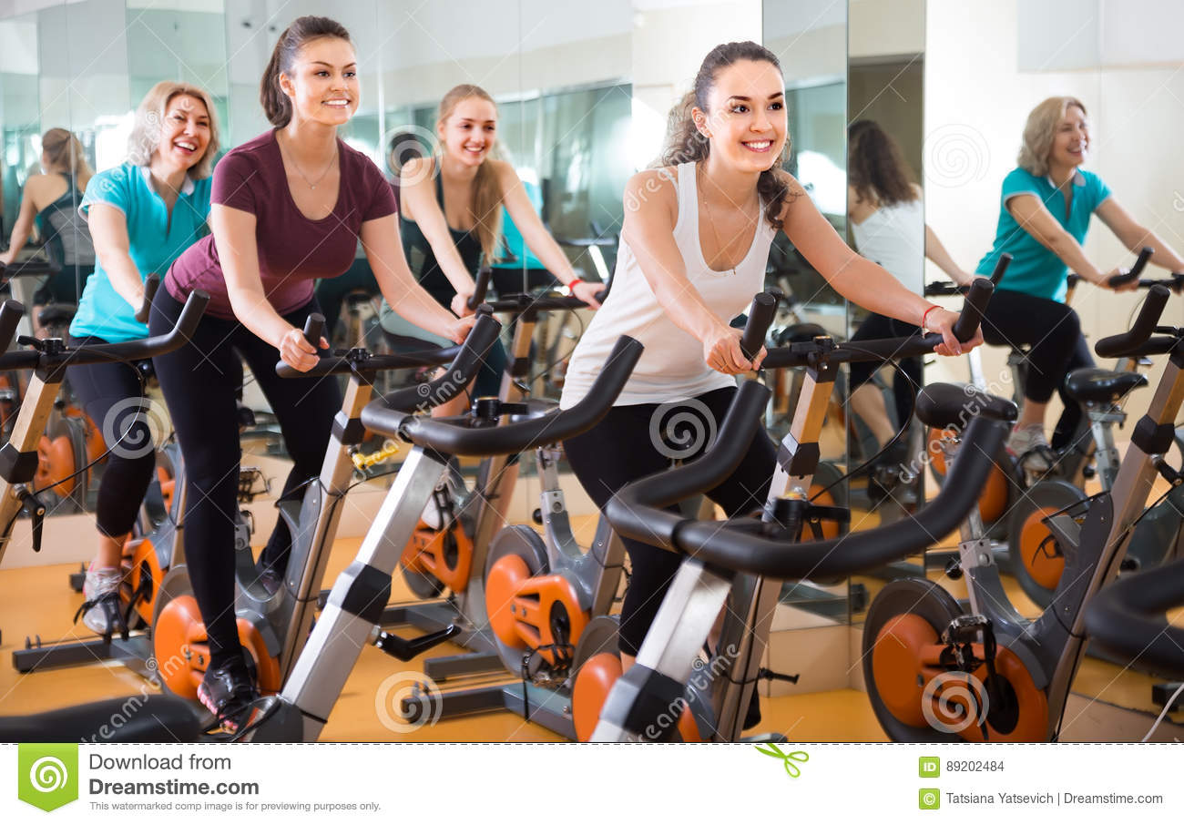 Several Women Of Different Age Training On Exercise Bikes Stock