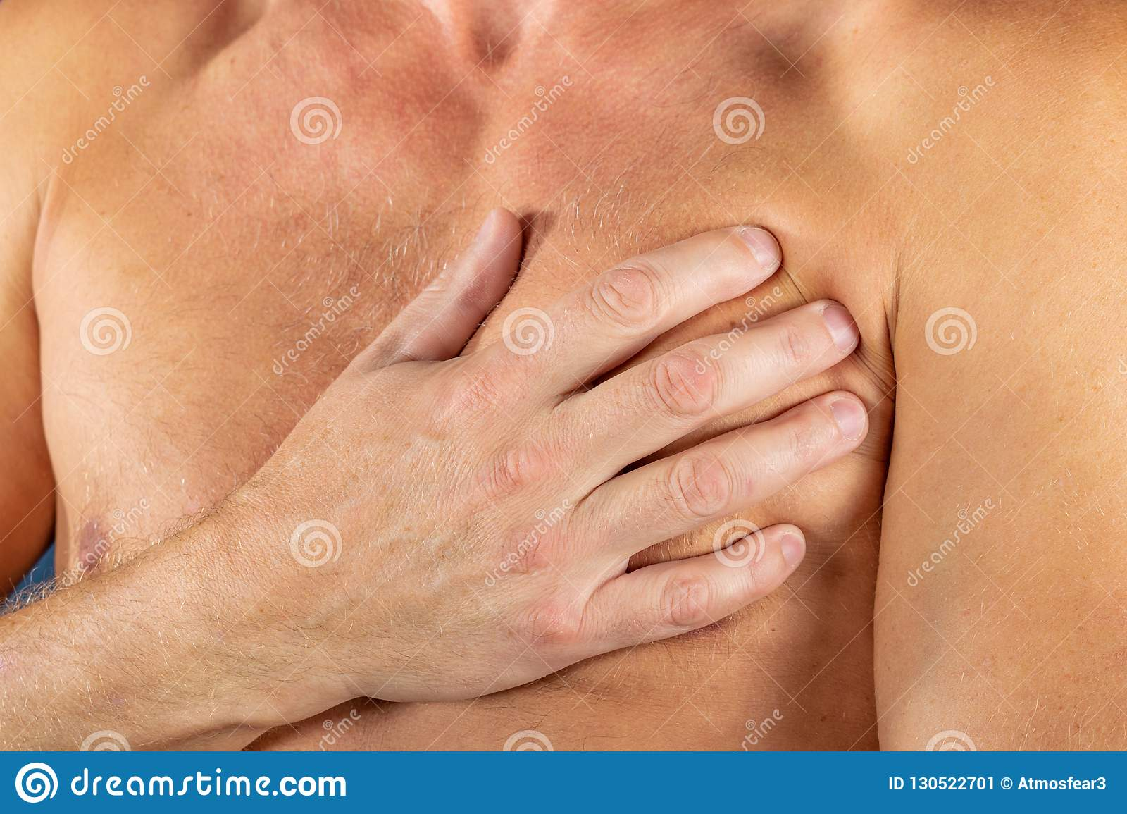 Man suffering from chest pain, having heart attack or painful cramps, pressing on chest with painful expression on blue backgound.