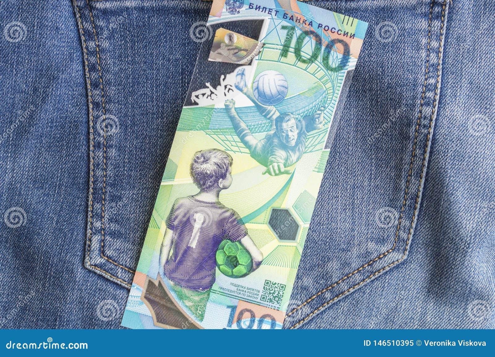 04 21 Severodvinsk 2019 Ryssland Ryska jubileumsedlar av den FIFA fotbollvärldscupen 2018 100 rubel på jeansbakgrund