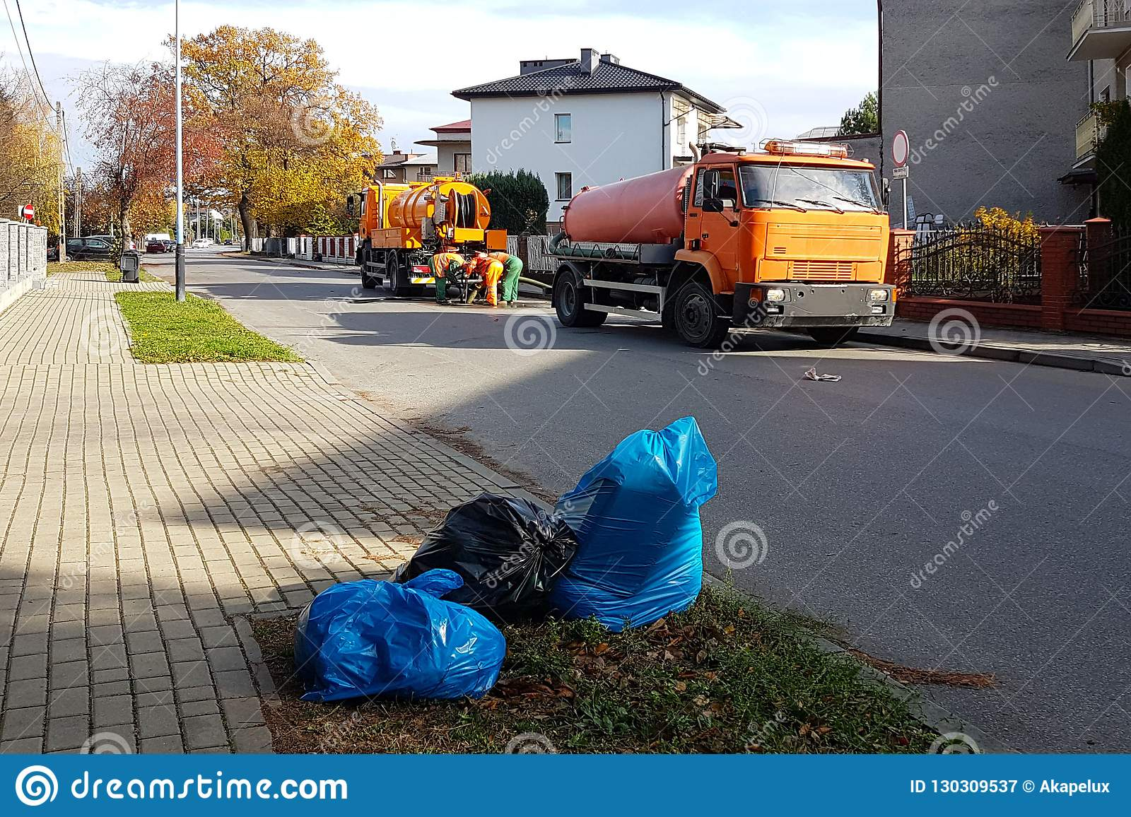 Sewage clearing by special technical means on the streets of a small European town. Orange cars and municipal workers clean the ci
