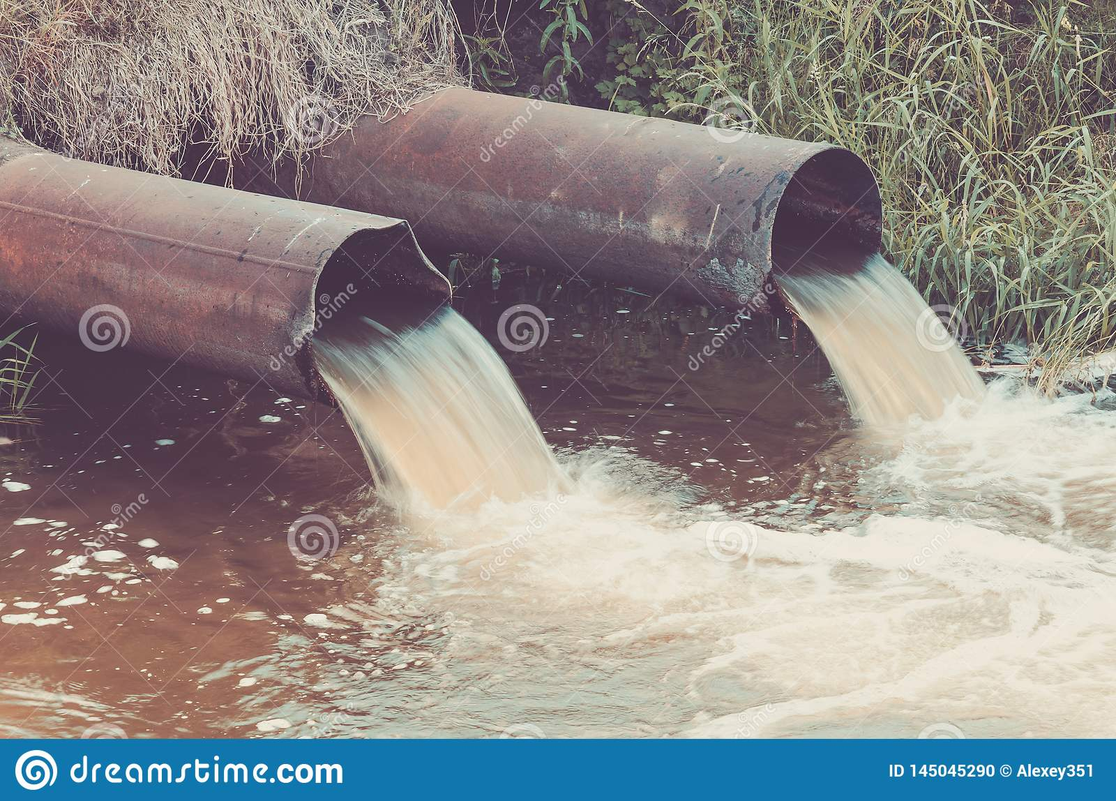 sewer pipes pour out to the river/sewer pipes pour out to the river. Toned