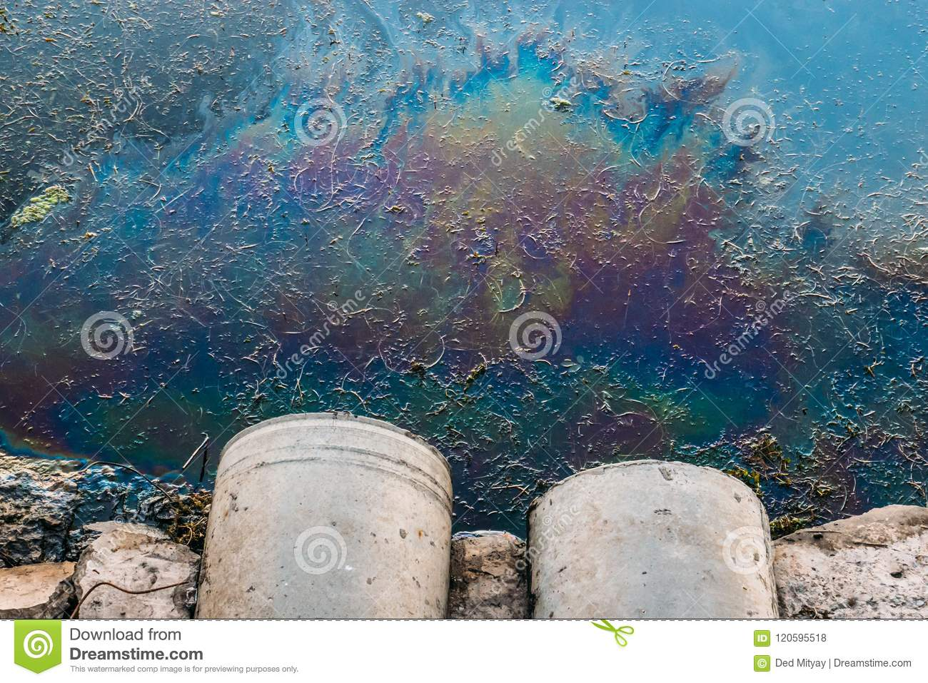 Sewer pipes at shore, stain of oil or fuel on water surface, nature pollution by toxic chemicals, dirty sea