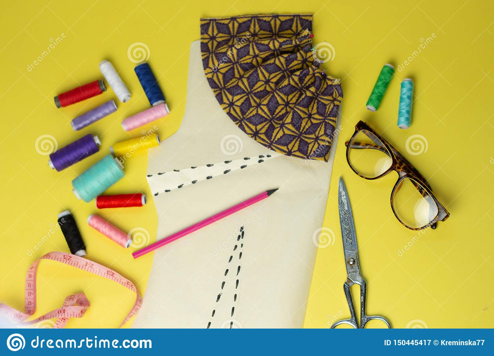 Sewing accessories and fabric on a yelow background. Sewing threads, pins, pattern and sewing centimeter. For sewing at home.Top