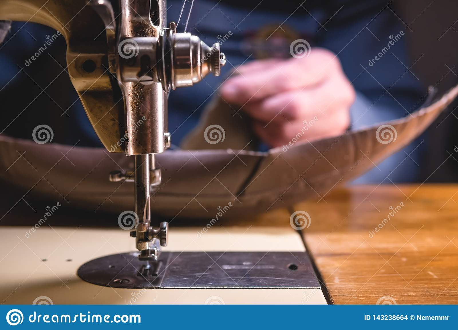 Sewing process of the leather belt. old Man`s hands behind sewing. Leather workshop. textile vintage sewing industrial