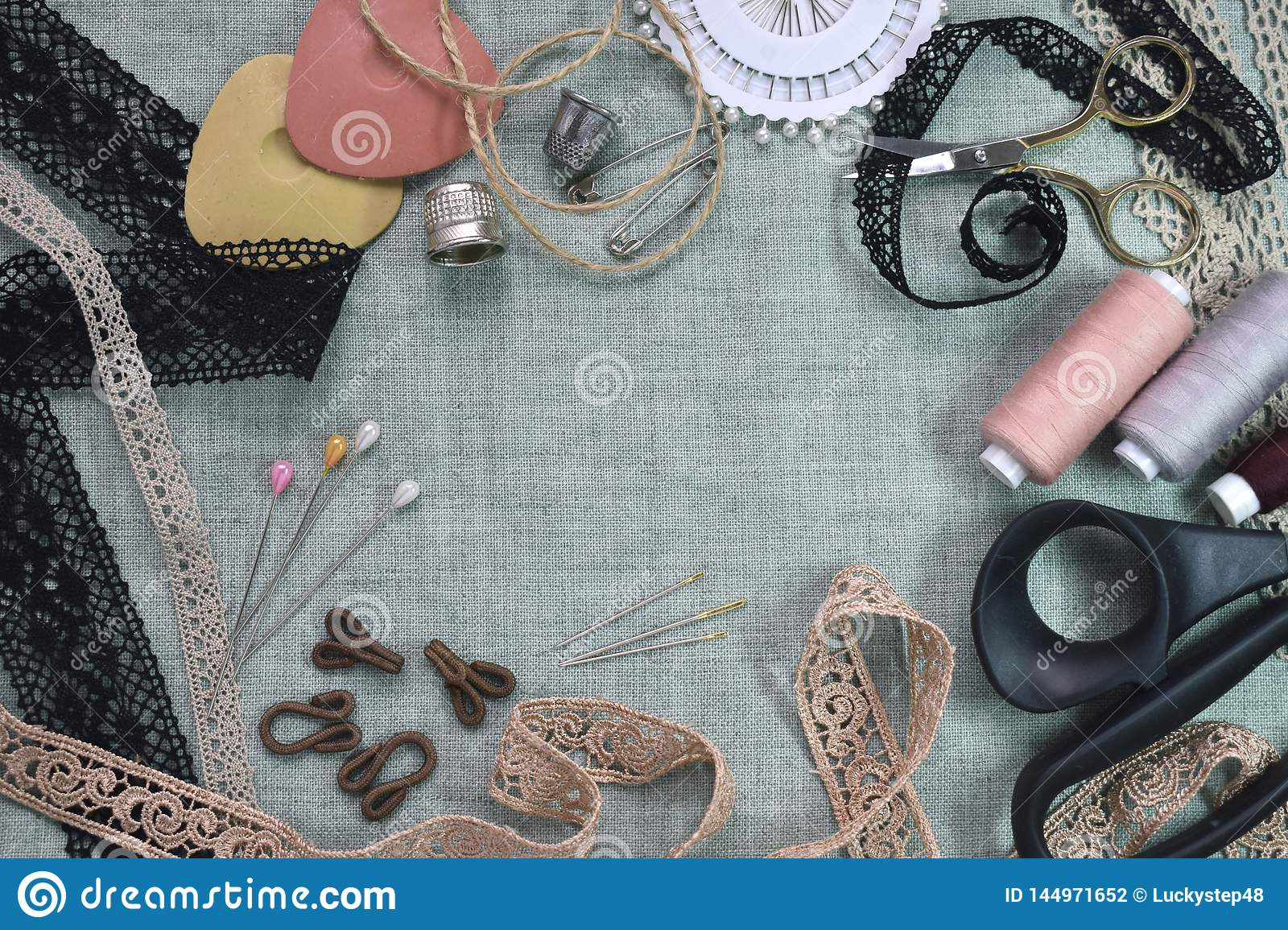 Sewing scene table flat lay composition. Threads, lace, pins, scissors, tape, reel, cloth. Pastel colors linen fabric