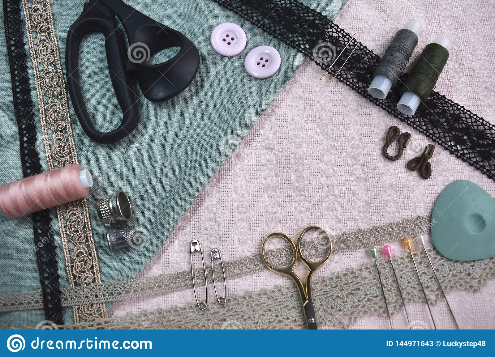 Sewing scene table flat lay composition. Threads, lace, pins, scissors, tape, reel, cloth. Pastel colors rose pink light