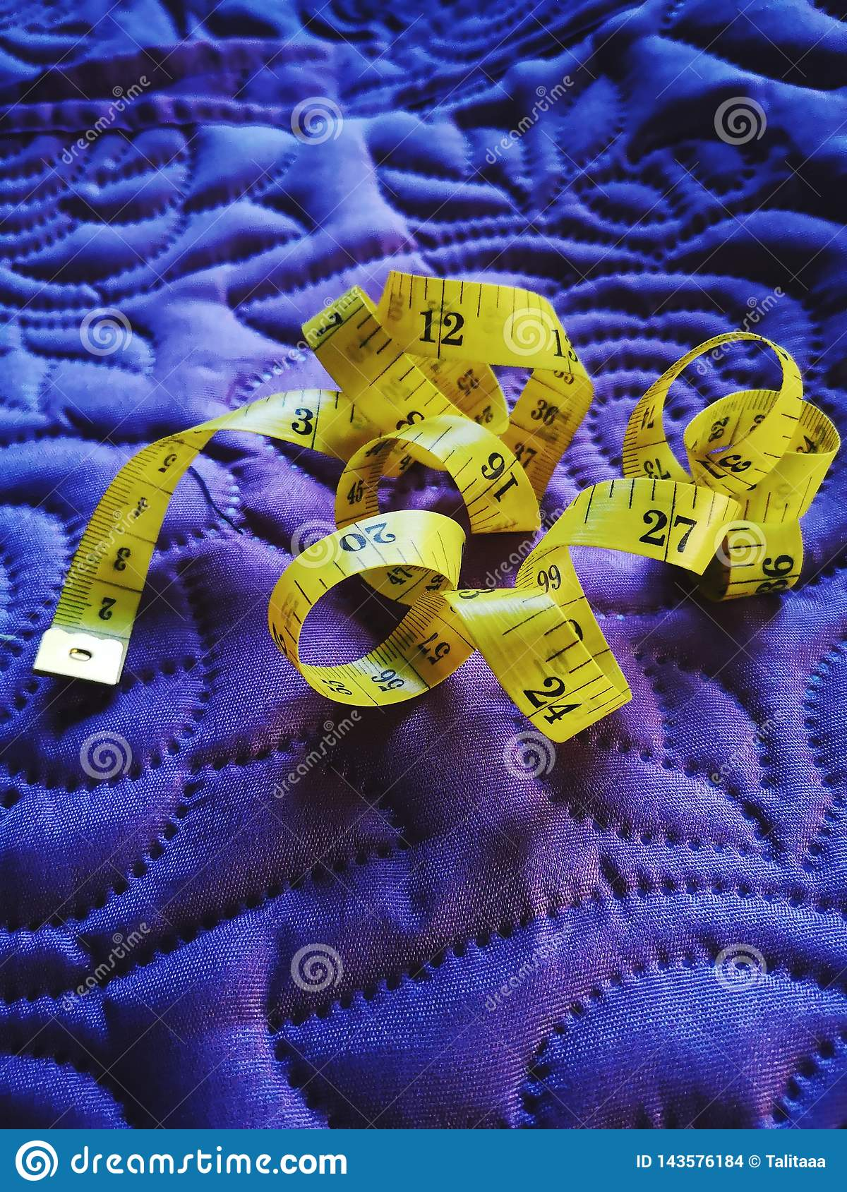 Sewing. yellow measuring tape for sewing on purple material