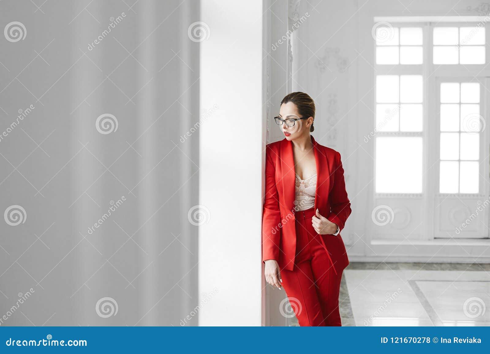 Sexig affärsdam, plus formatmodellflicka i stilfulla exponeringsglas och i den röda trendiga dräkten som poserar nära fönstret på