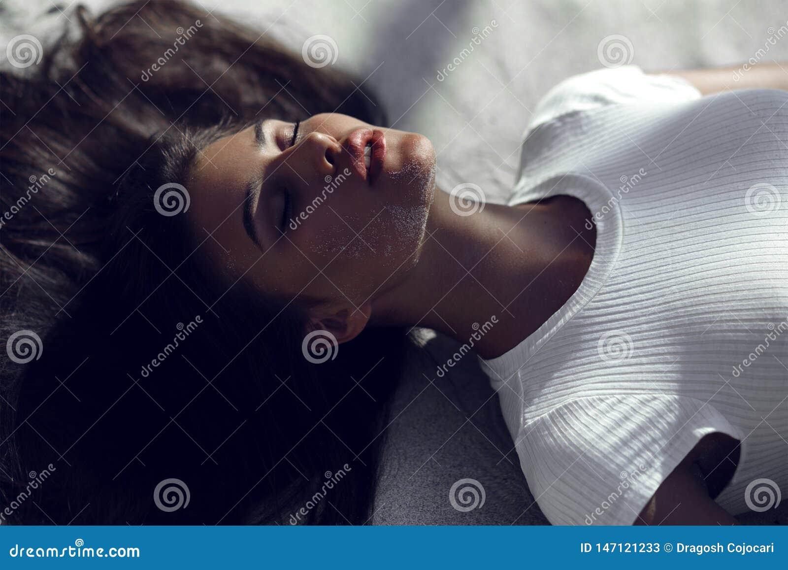 Sexig brunbränd brunettflicka med stängda ögon och stora sinnliga kanter som ligger på stranden på vit sand med skuggor på framsi