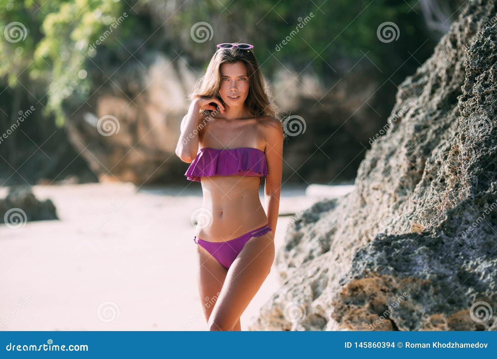 Sexig brunbr?nd flicka i den purpurf?rgade baddr?kten som poserar p? stranden med sand och stora stenar