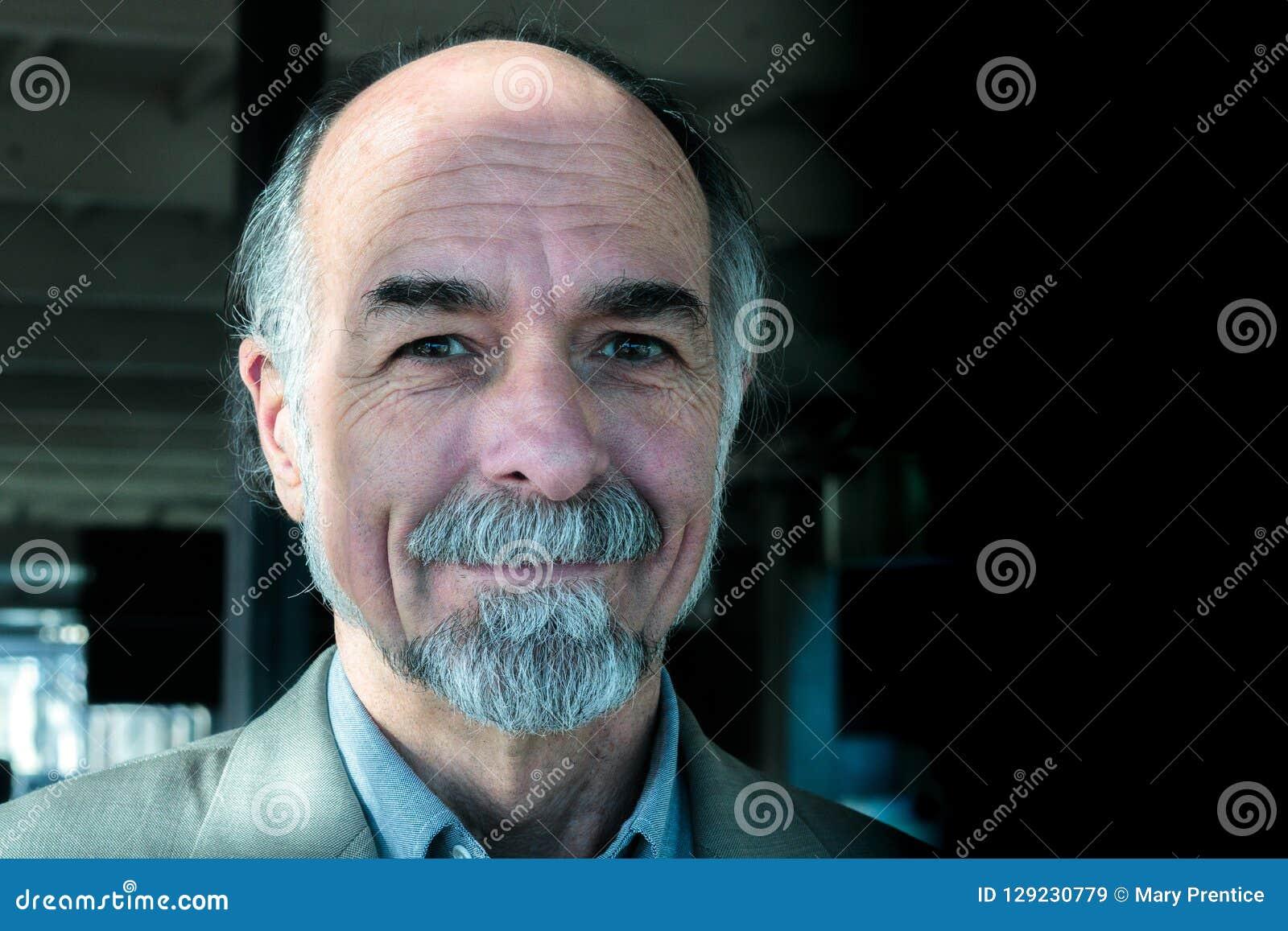Sexig charmig attraktiv hög vuxen man i 60-tal som ler på kameran med att gråna pärlan, skrattgropar, bruna ögon, sund hög man p