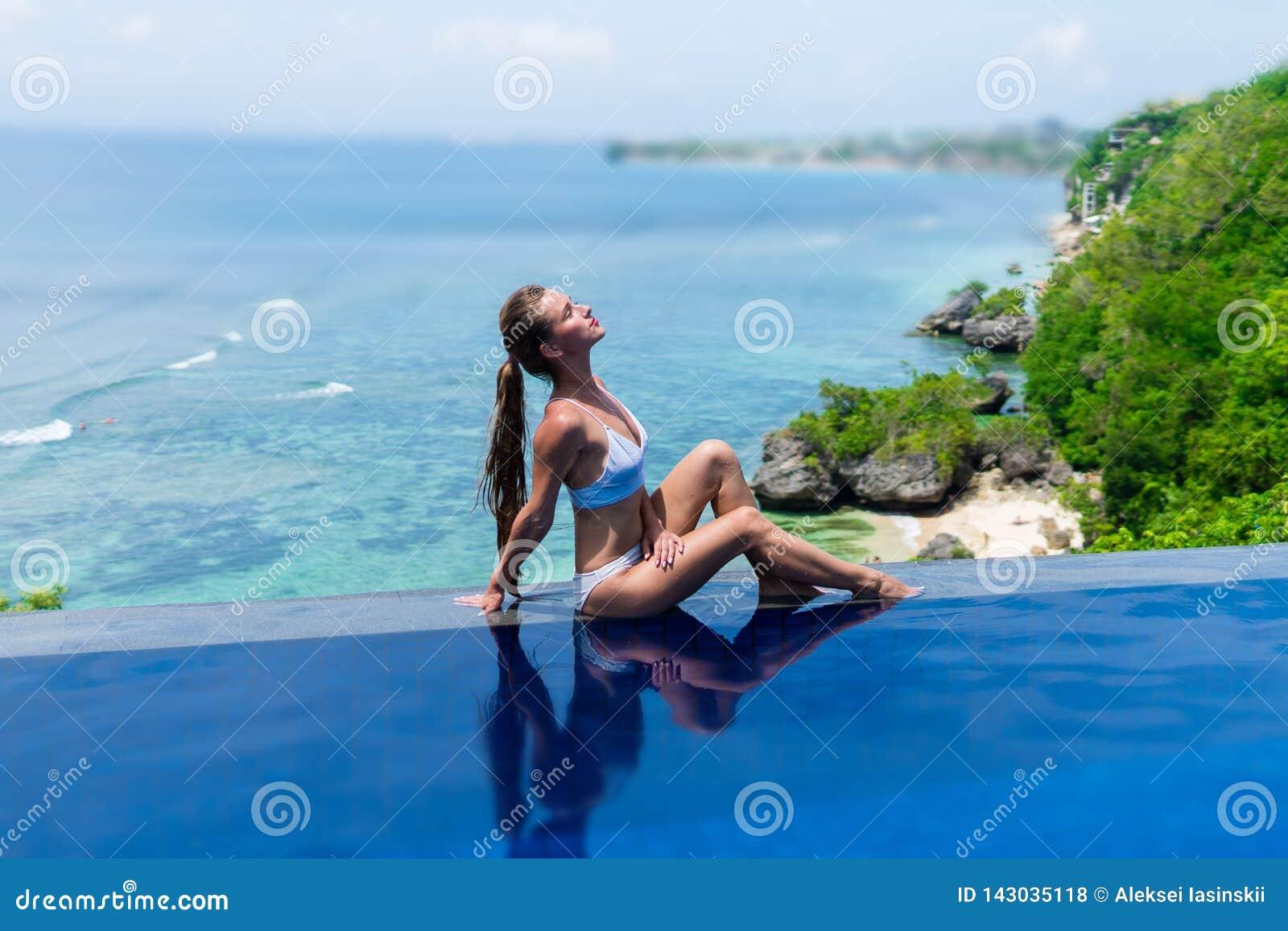 Sexig flicka härlig kvinna underkläderna för modelldambikinin sitter kanten av vattenbadpölen på taket av hotellet för den lyxiga