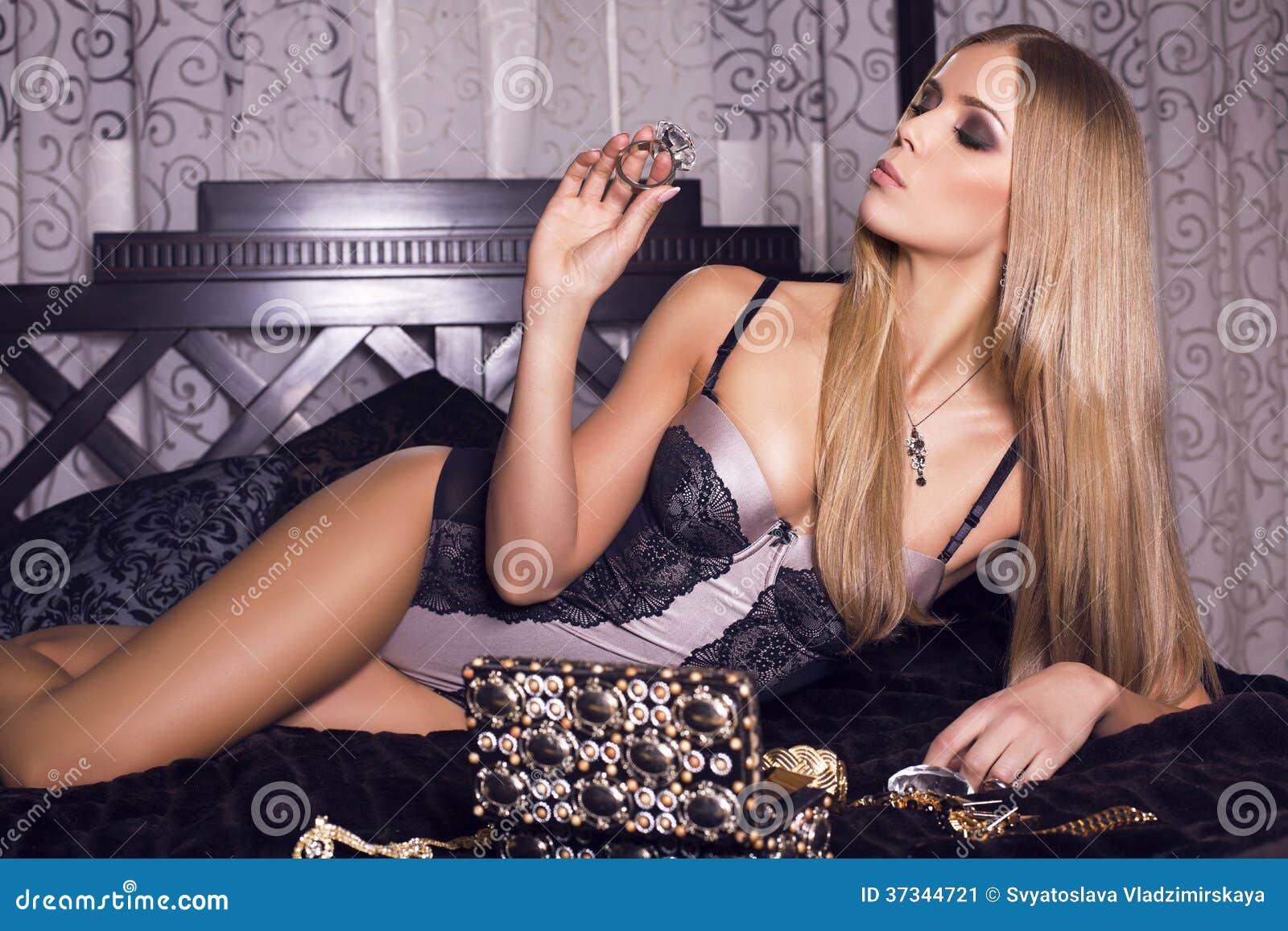 Sexig flicka med blont hår i damunderkläder som ligger på sängen