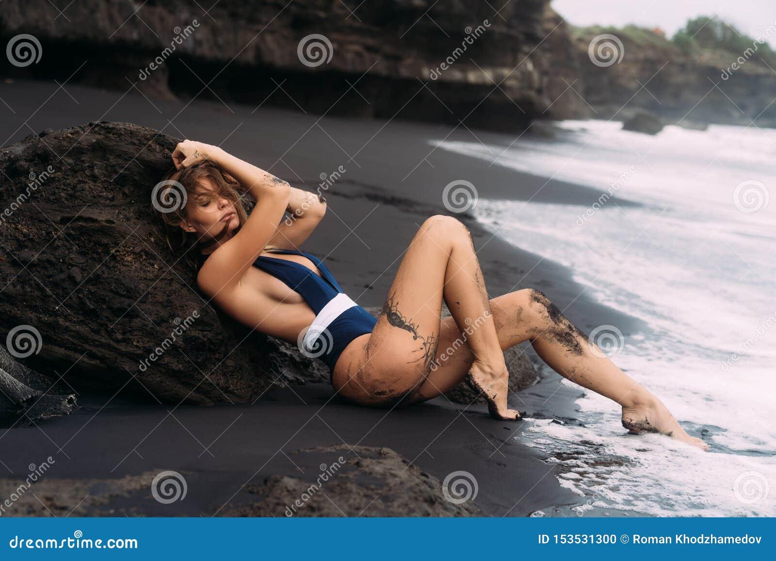 Sexig flicka med stora br?st i bl? swimwear som kopplar av p? stranden med svart sand