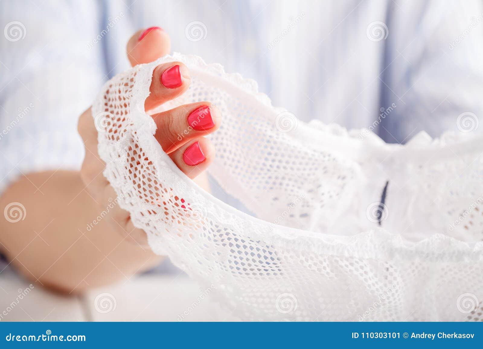 Sexig genomskinlig underbyxor på vit bakgrund i kvinnliga händer