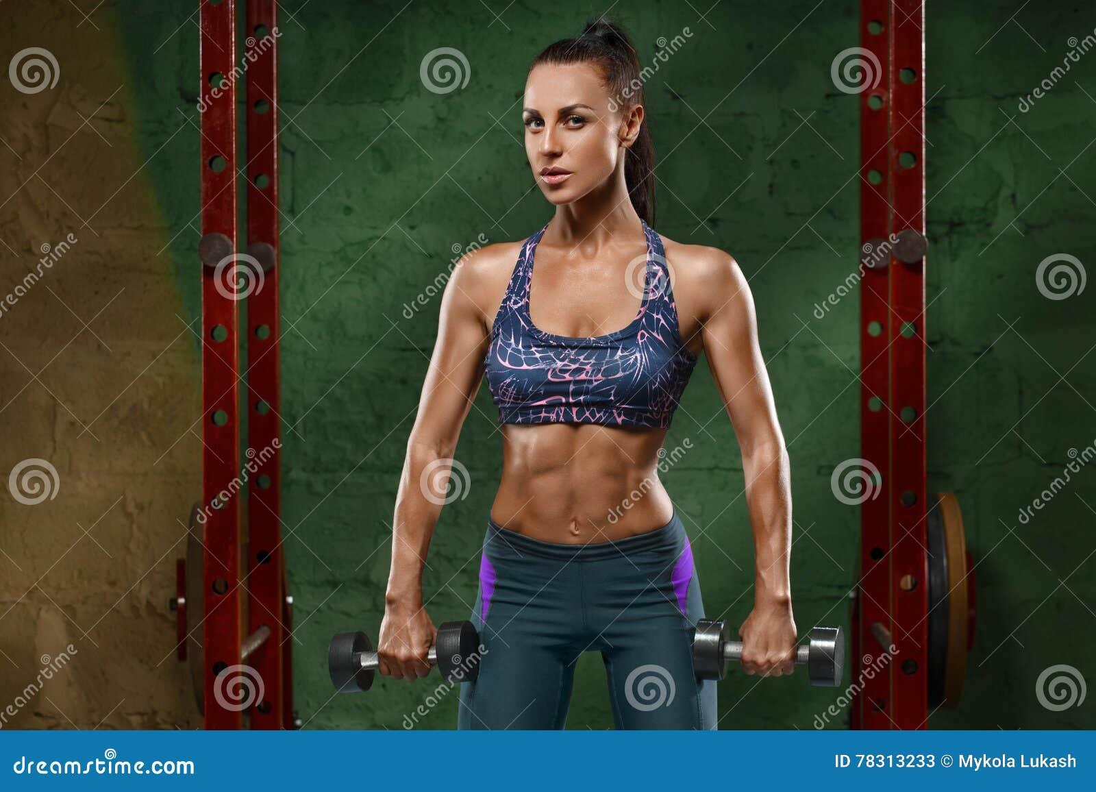 Sexig konditionflicka som utarbetar i idrottshall Muskulös kvinna, abs, format buk-