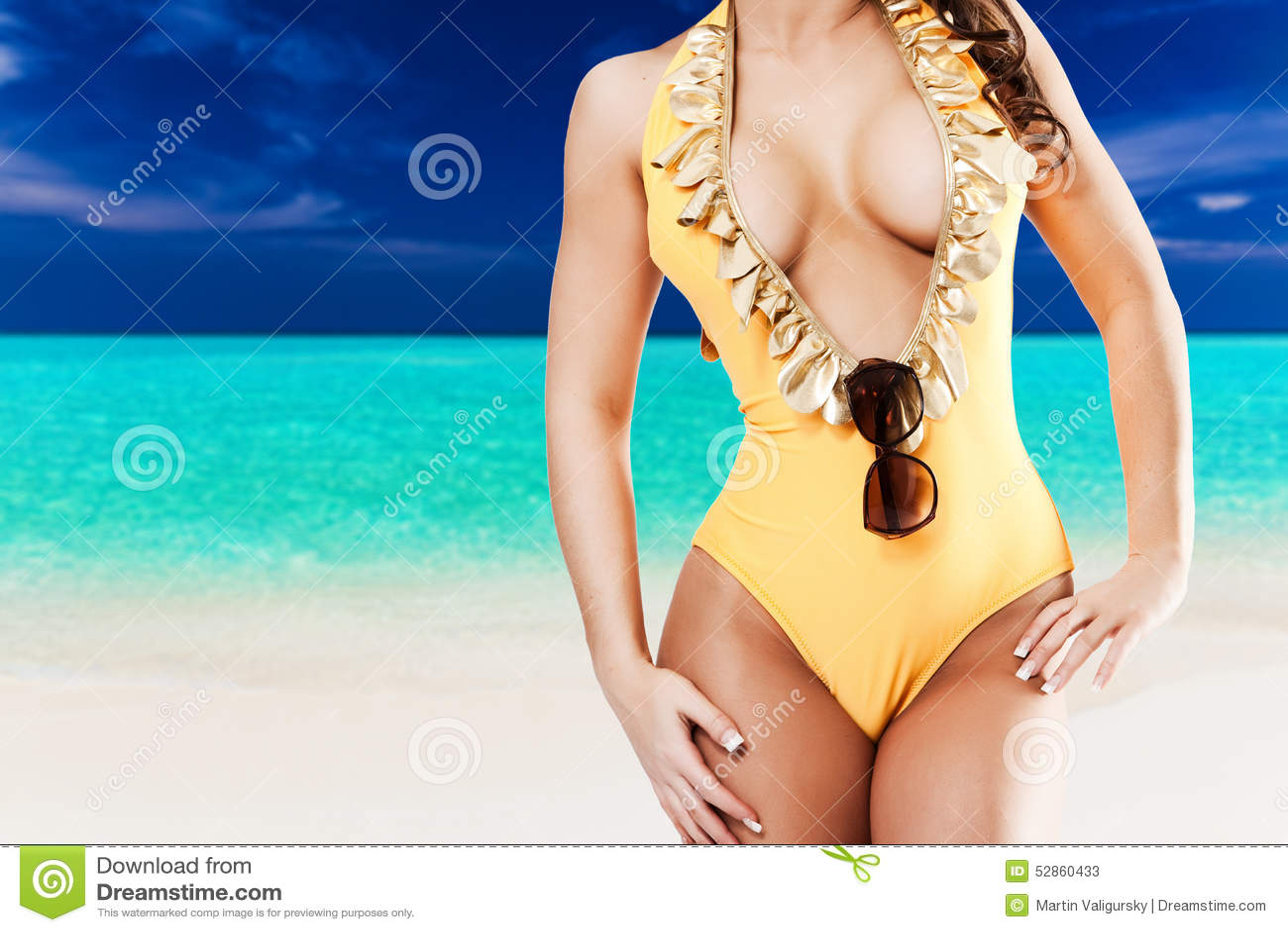 Sexig kvinna i gul bikini framme av den tropiska stranden med blått