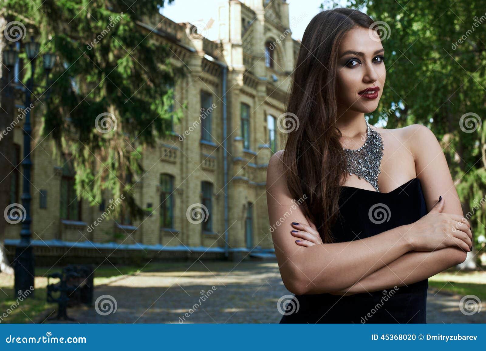 Sexig kvinna i svart klänning och halsband