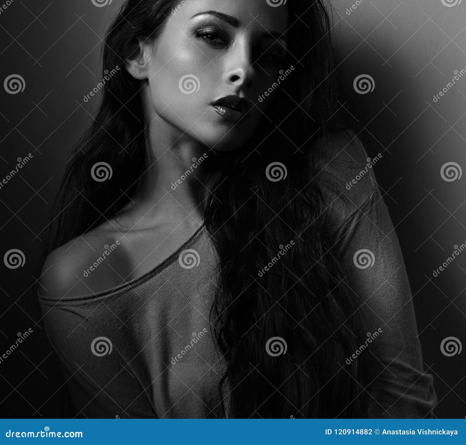 Sexig kvinna med röd läppstift som poserar i svartbackgro för mörk skugga