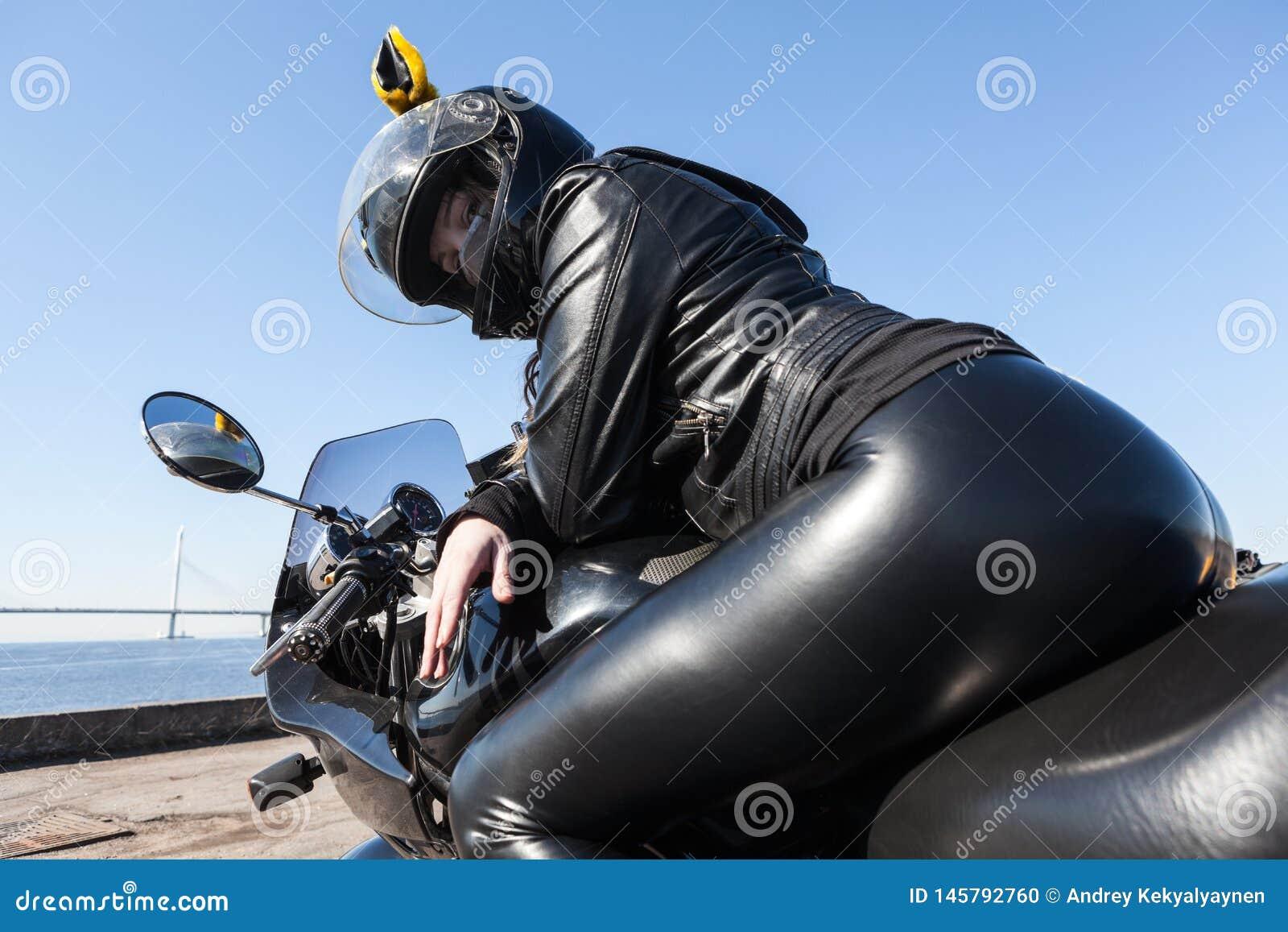 Sexig kvinnamotorcyklist i svart läderdräkt och hjälm som sitter på cykeln, bakre sikt, sikt för låg vinkel