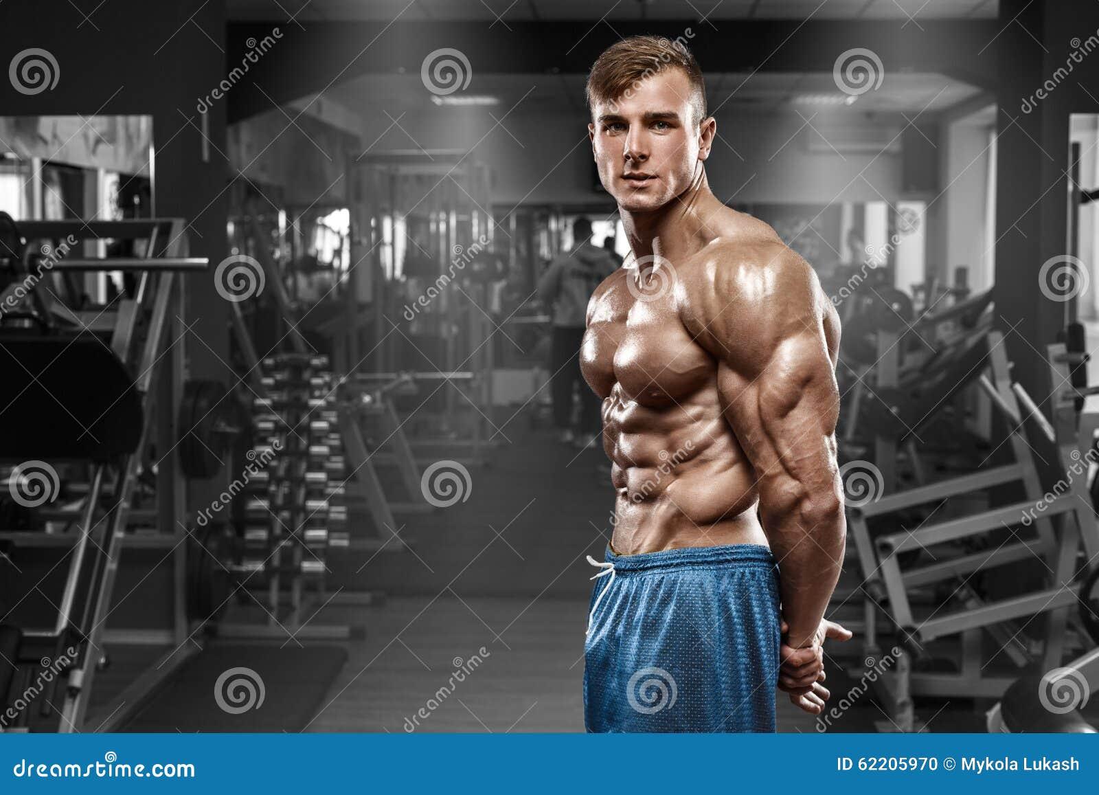 Sexig muskulös man som poserar i idrottshallen, format buk- som visar triceps Stark manlig naken torsoabs som utarbetar
