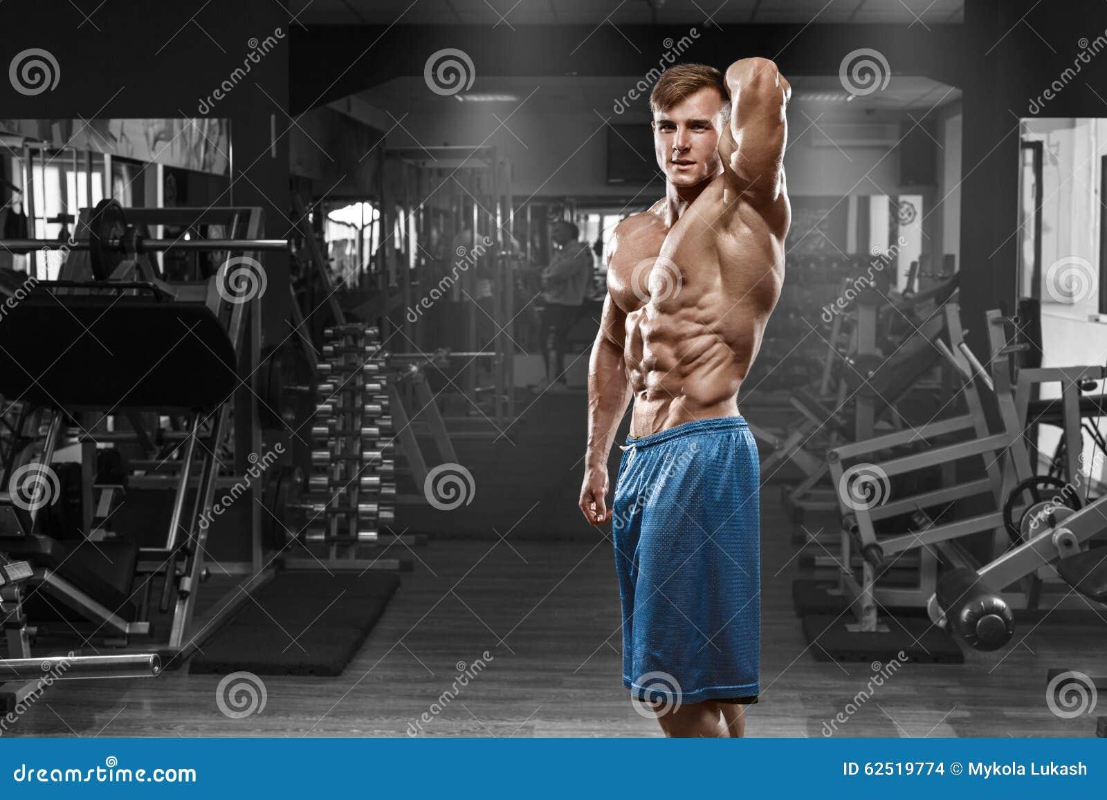 Sexig muskulös man som poserar i idrottshallen, format buk- Stark manlig naken torsoabs som utarbetar