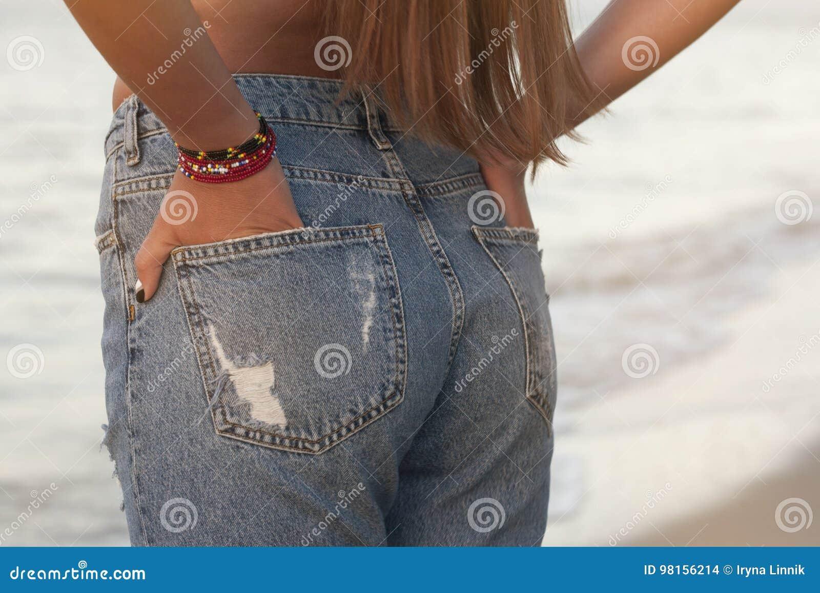 Sexig perfekt kvinna i jeans mot havet tillbaka sikt Mellersta kroppsdelar Mode Advertizing av trendig jeans