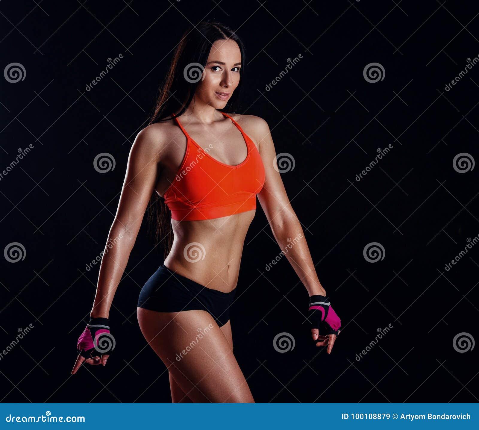 Sexig slank kvinnlig för härlig kondition i activewearen som poserar över svart bakgrund