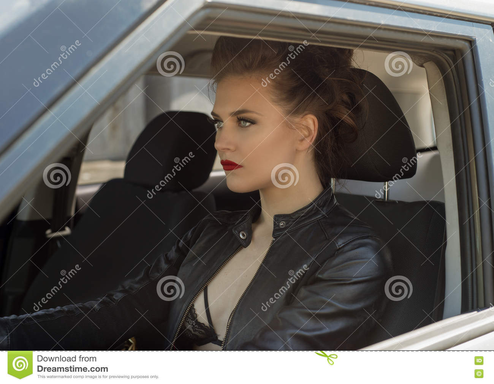 Sexig ung flicka som kör bilen i läderomslag