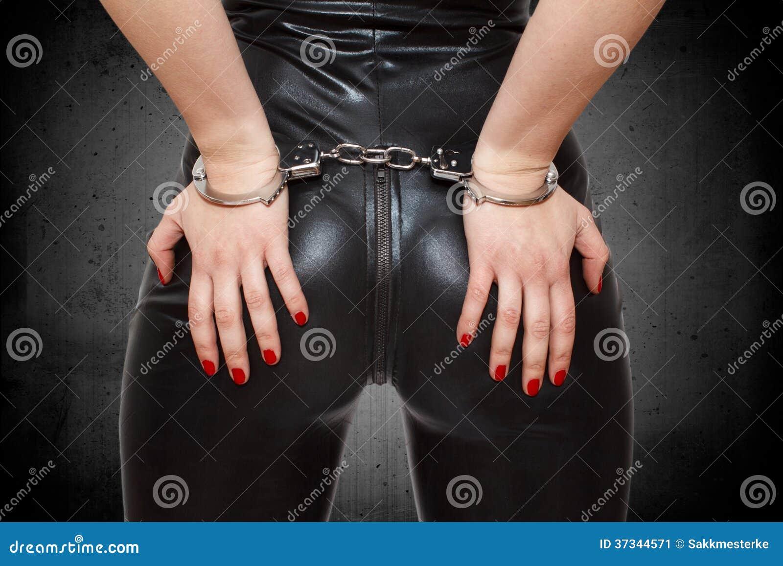 Sexiga dominatrixhänder på röv i handbojor