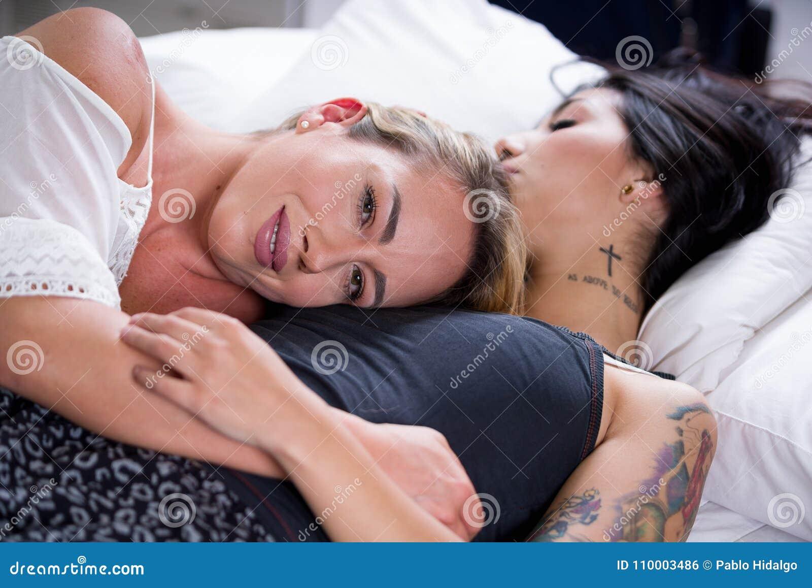 Sexiga lesbisk kvinnavänner i säng på morgonen, den blonda flickan sover över brunettflickabröstkorgen, i en vit bakgrund