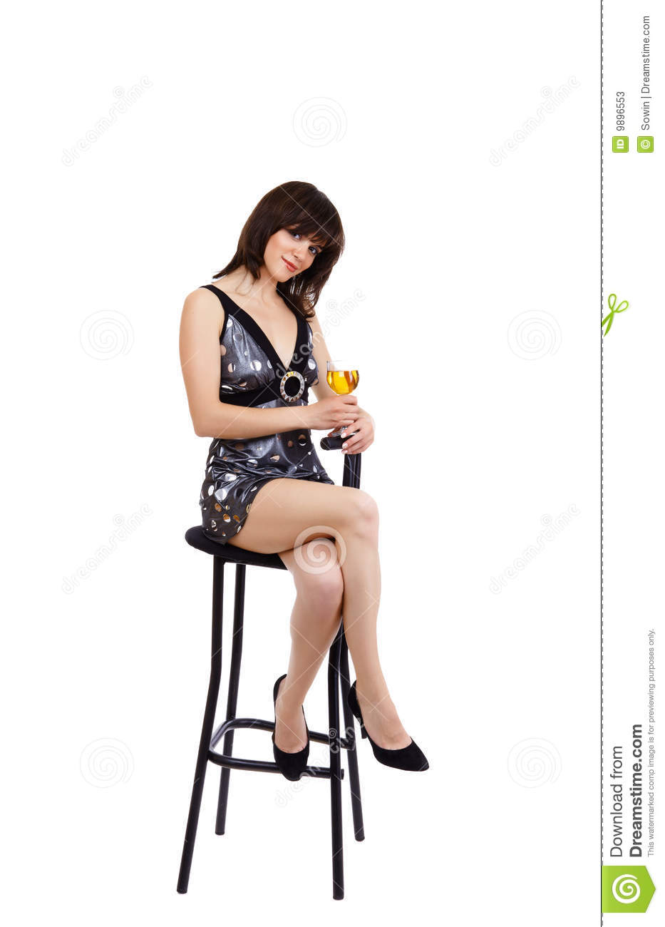 The sexual girl sits on a bar chair