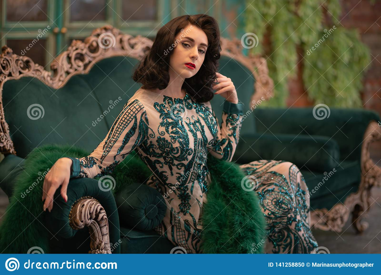a78e569109 Elegant caucasian girl in a luxurious long sequins lace dress with a green  fluffy boa in