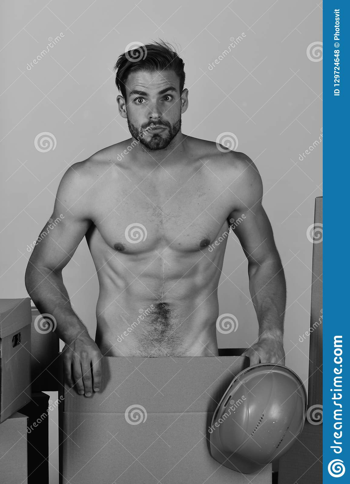Sexuality and building concept: guy with body holding helmet