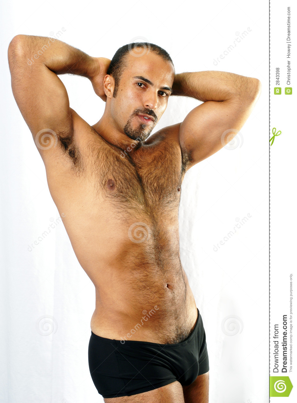 This image shows a muscular Hispanic man with trimmed chest hair in a  sexualized pose.