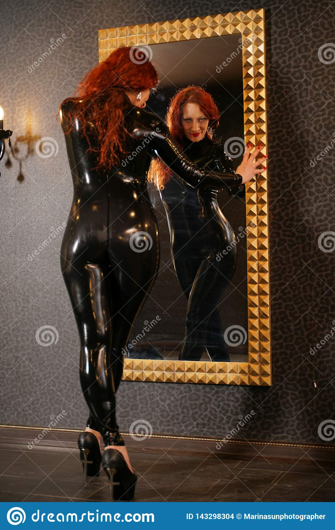 Sexuell fetischrödhårig mankvinna som bär svart latexgummicatsuit och ser spegeln i mörkt rum
