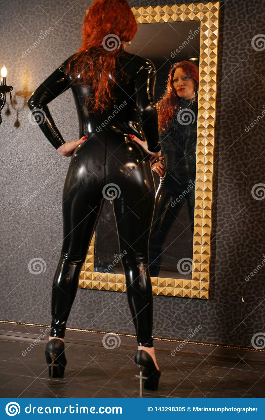 Sexuelle Fetischrothaarigefrau, die schwarzes Latex catsuit trägt und den Spiegel in der Dunkelkammer betrachtet