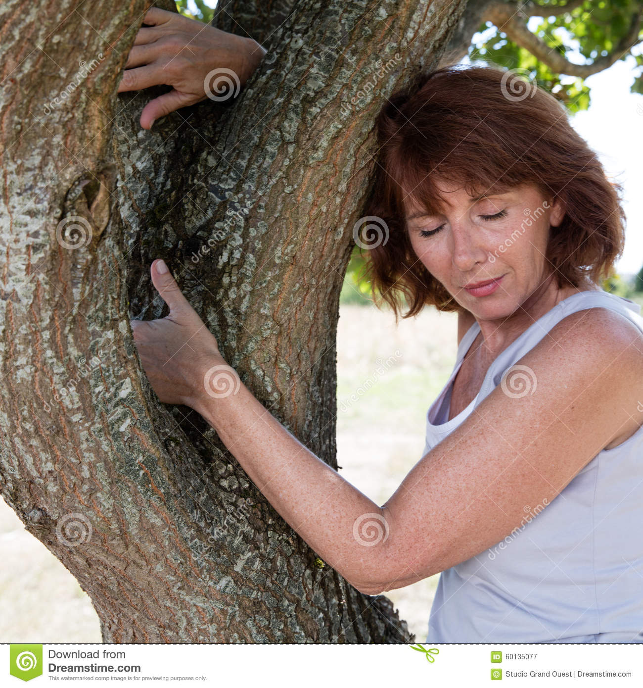 aging woman touching a tree for wellbeing stock image - image of