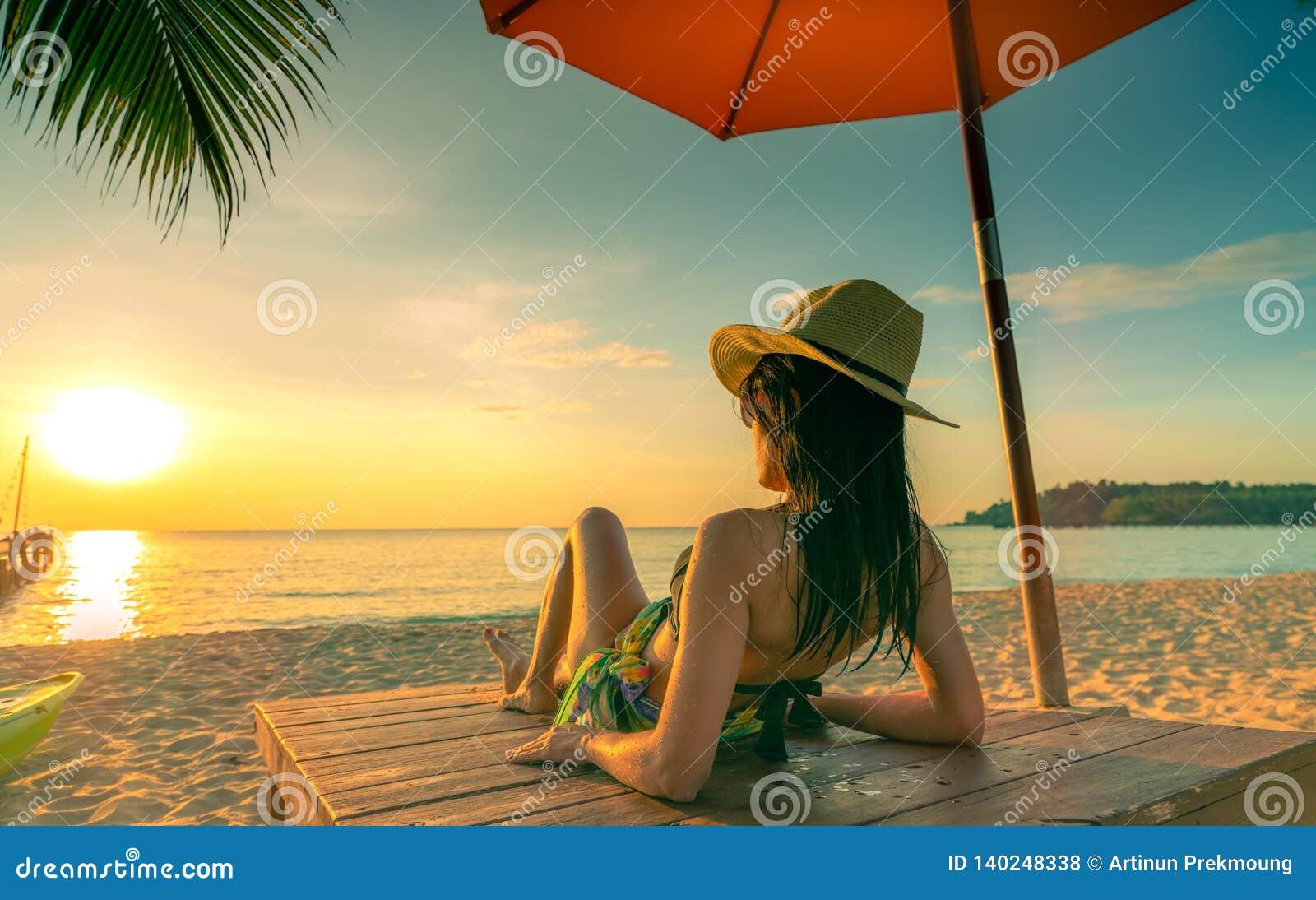 Sexy, appréciez et détendez le bikini d usage de femme se trouvant et prenant un bain de soleil sur le lit pliant à la plage de s
