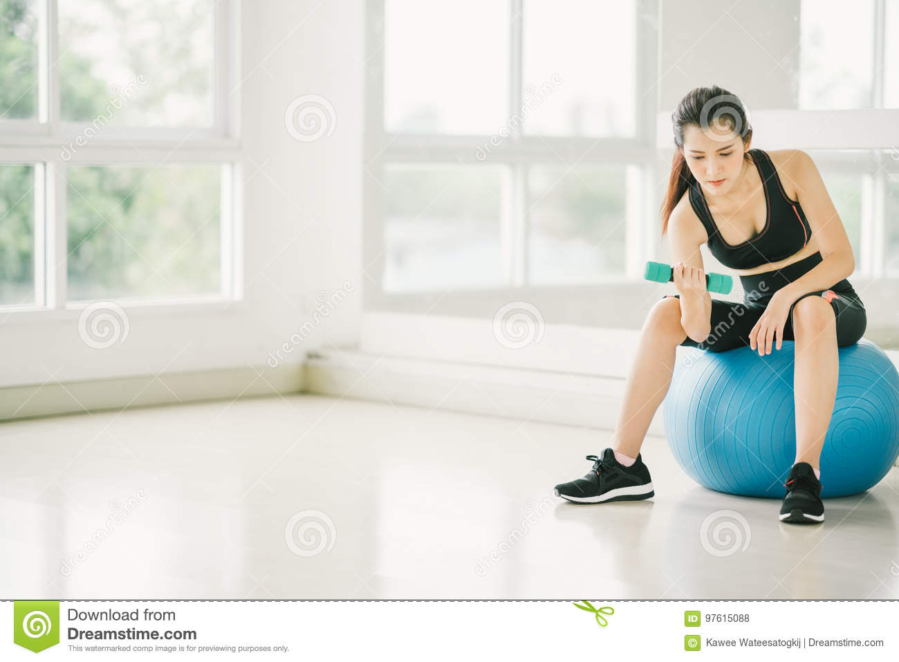 Asian girl exercising with dumbbell on fitness ball at fitness gym with copy space, sport and healthy lifestyle